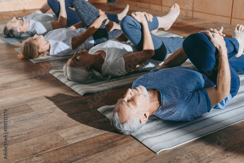 Door stickers Yoga school group of senior people stretching in yoga mats in studio