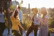 Female friends dancing and drinking at a rooftop party