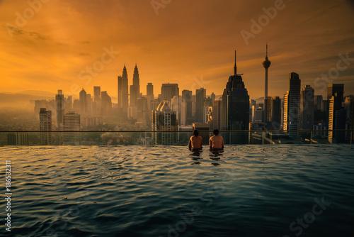 Fototapeta  Two traveler man looking view skyline Kuala Lumpur city in swimming pool on the roof top of hotel at sunrise in Kuala Lumpur, Malaysia
