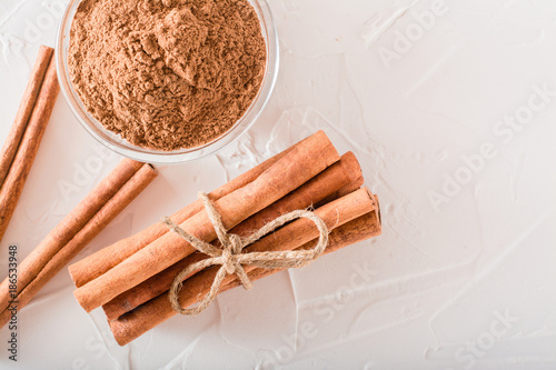 Photographie Cinnamon sticks, tied with a rope, and ground cinnamon in a bowl lie on the table