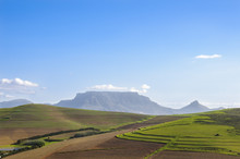 View Of Table Mountain In Cape Town, South Africa Over Vistas Of Wine Lands And Vineyards On A Sunny Day With Clear Blue Skies And Scattered Clouds.