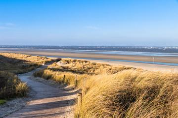 Weg durch die Dünenlandschaft zum breiten Strand auf der Nordseeinsel Spiekeroog im Winter