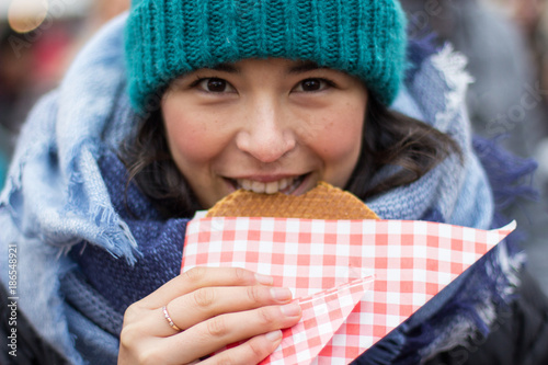 Photo  A Hispanic girl eating a local waffle in Utrecht, Netherlands.