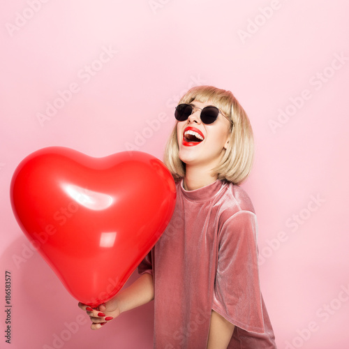 Photo  Sexy blonde hugging in the shape of a heart a red ball and smiling