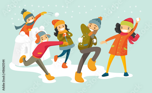 Obraz na plátně Young happy caucasian white family playing snowball fight and having fun in snow in winter