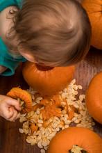 A Child Peeking Inside A Pumpkin