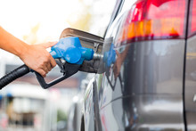 Hand Refilling The Car With Fuel At The Refuel Station.