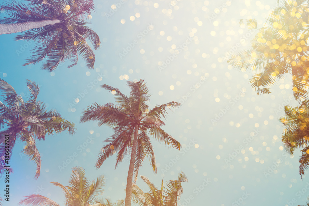 Palm trees vintage toned with shiny party bokeh lights effect