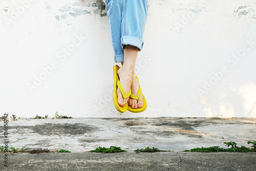 Yellow Sandals. Woman Wearing Flip Flops and Blue Jeans Standing on Old Cement Floor Background Great for Any Use.