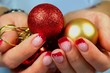 Young woman holding Christmas ornaments in her hands./Christmas is here.Young woman holding red and gold Christmas ornaments in her hands with beatiful nails.