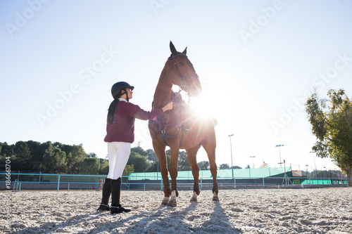 Young girl standing with chestnut horse and preparing to ride in backlit.