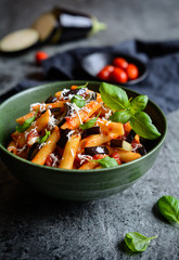 Traditional Italian Pasta alla Norma with eggplant, tomato, cheese and basil