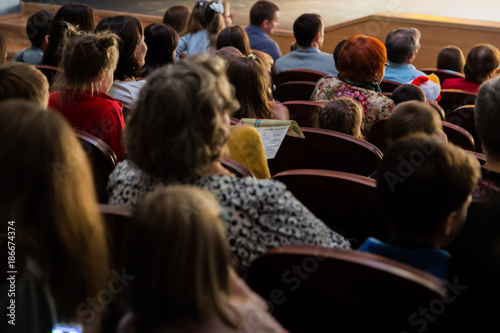 People, parents with children in the audience watching a children's show. Sold out. Shooting from the back.