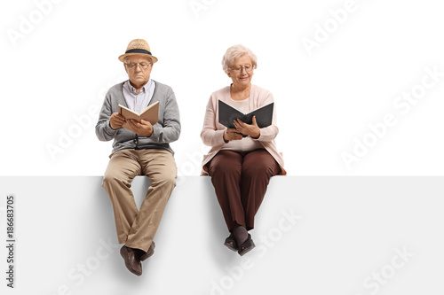 Mature man and an elderly woman sitting on a panel and reading books