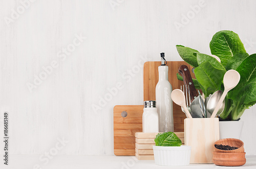 Fotografía  Natural beige and brown wooden kitchenware and green plant on light white wood background, copy space