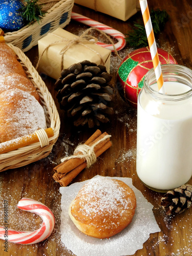 Foto op Plexiglas Milkshake Donut berliner and a glass of milk surrounded by Christmas attributes on a wooden background