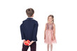 back view of boy in fashionable suit holding heart shaped gift box and looking at beautiful little girl in pink dress isolated on white