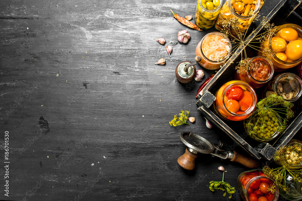Fototapety, obrazy: Preserved vegetables and mushrooms in a box with seamer.
