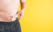 Man is measuring his body fat with calipers,healthy lifestyle and body care concept.