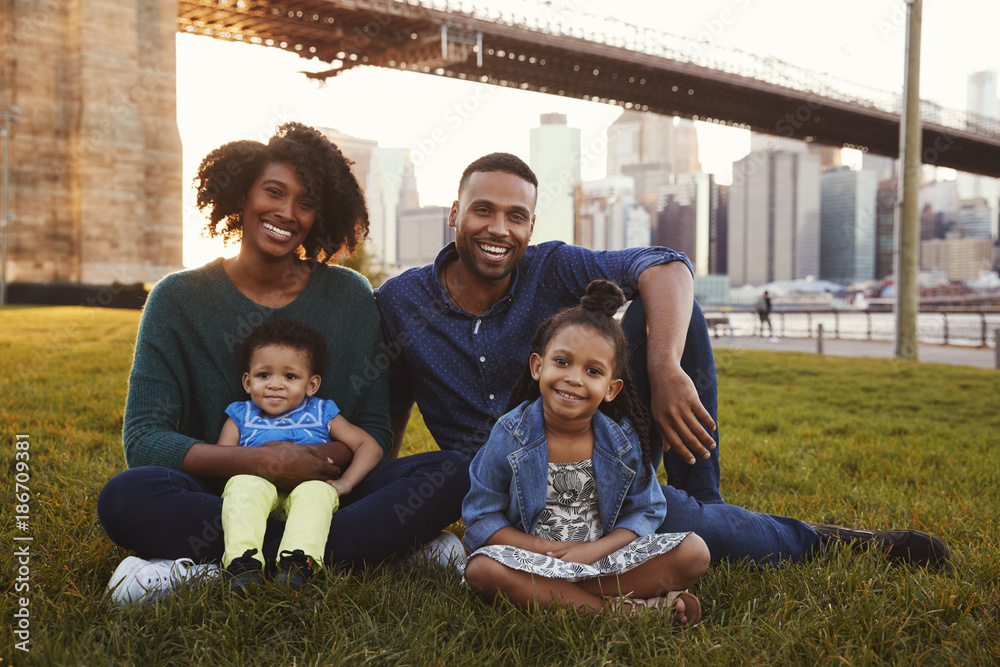 Fototapety, obrazy: Young family with two daughters sitting on lawn, close up