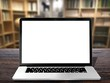 Laptop with blank white screen on wooden table - blurred room background