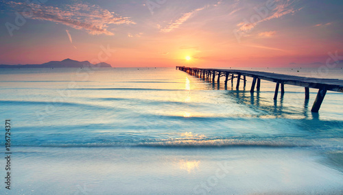Obraz Długa promenada na plaży o zachodzie słońca - fototapety do salonu