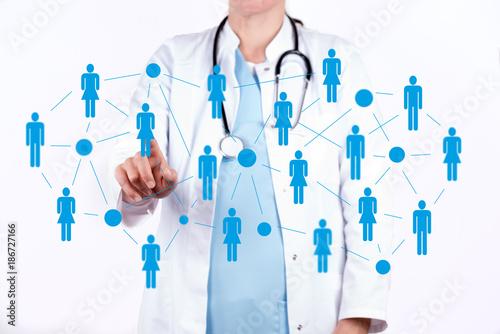 Foto  Arzt vor einer virtuellen Wand mit einem Netzwerk von Patienten