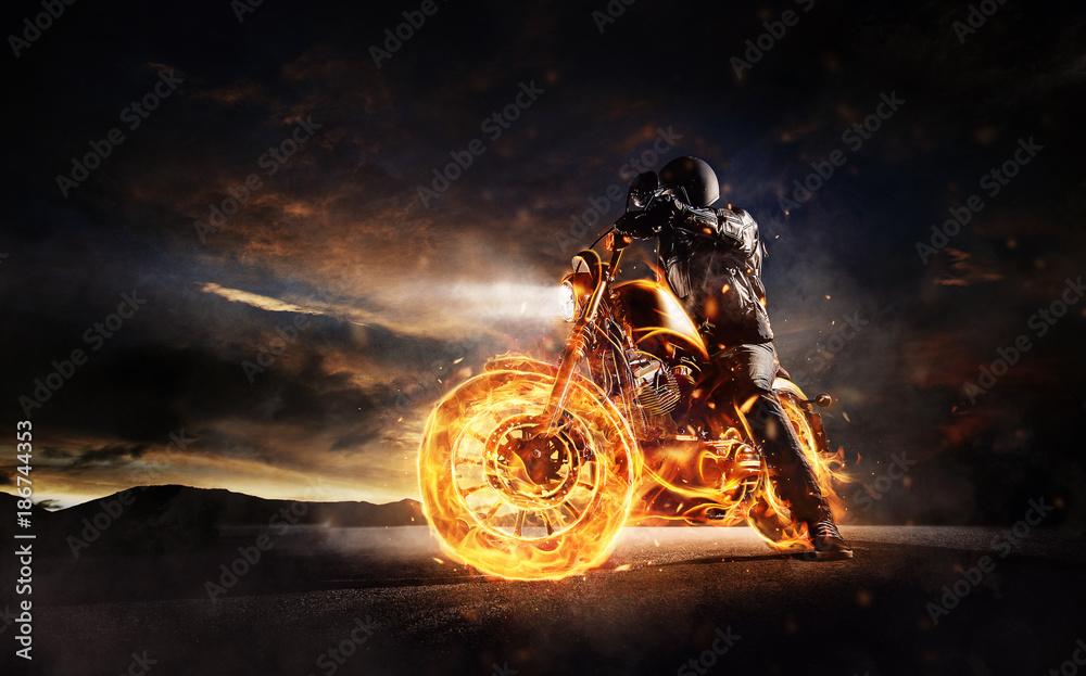 Fototapeta Dark motorbiker staying on burning motorcycle in sunset light