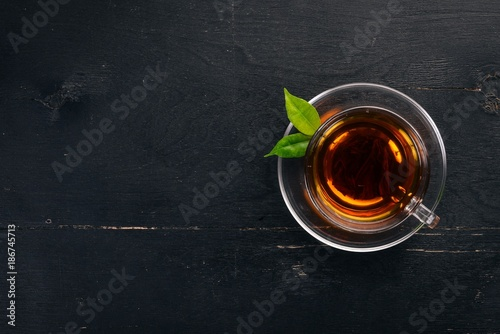 Photo sur Toile The A cup of black tea on a wooden background. Top view. Copy space.