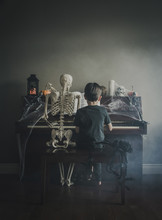 Rear View Of Boy Playing Piano While Sitting By Skeleton During Halloween