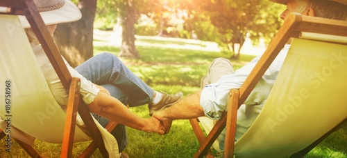 Fotografía Mature couple sitting in deck chairs at park