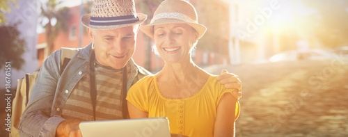 Foto  Happy tourist couple using tablet pc in the city