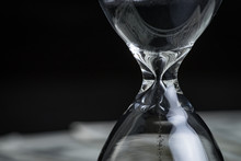 Closed Up Of Sandglass Or Hourglass With Reflection Of US Dollar Banknotes On Black Background Using As Time Investment Or Financial Deadline Concept