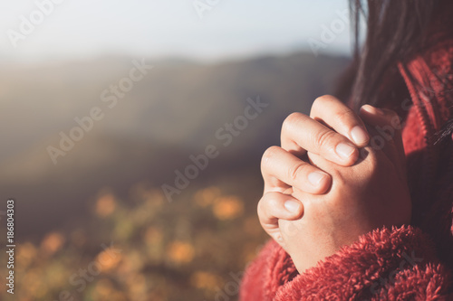 Foto Woman hands folded in prayer in beautiful nature background with sunlight in vin