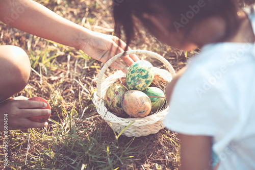 Two asian child girls playing and collecting colorful Easter eggs in basket together in outdoor in vintage color tone