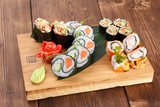 Fototapeta Tęcza - A wooden plate holding different types of sushi pieces. serving sushi and rolls on a wooden plate with ginger and wasabi.