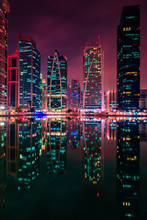 Jumeirah Lake Towers At Night Near Marina Dubai, UAE With Tall Business Buildings And Urban Lights
