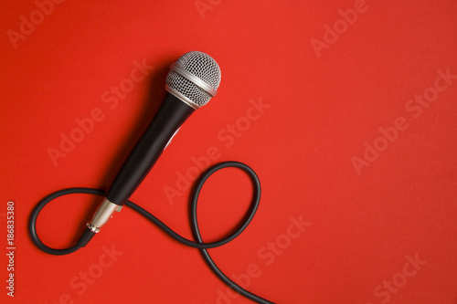 Photo microphone and lead on a bright red background.