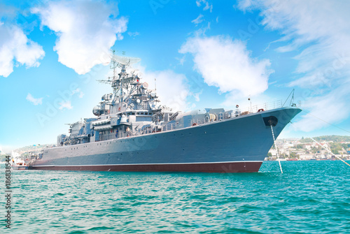 Fototapeta Military navy ship in the bay with blue sky and clouds
