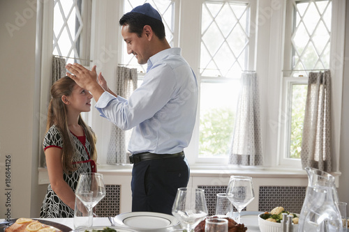 Photo Jewish father blesses daughter by table set for Shabbat meal