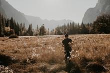 Man Walking On Dry Meadow