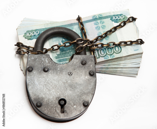 Fotografie, Obraz  Russian banknotes in a circuit under a large iron lock