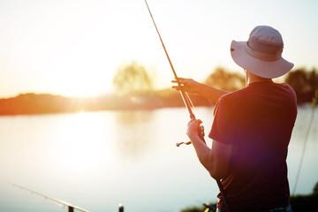 Mladić koji peca na jezeru u zalasku sunca i uživa u hobiju