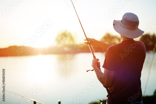 Stampa su Tela Young man fishing on a lake at sunset and enjoying hobby