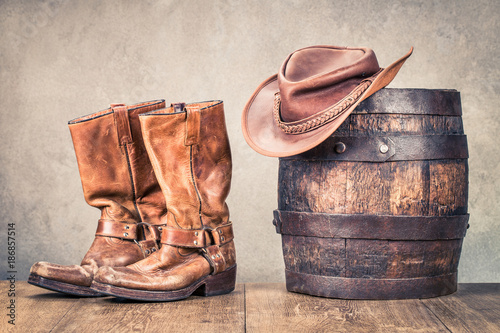 Valokuva  Wild West old retro leather cowboy boots, hat and oak barrel