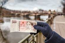 Czech Crown Banknote At The Background Of Prague City
