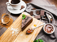 Chocolate Austrian Dessert Sacher With Apricot Jam, Mint Leaves And A Cup Of Coffee