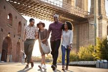 Group Of Friends Walking By Brooklyn Bridge In New York City
