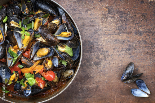 Valokuva  Traditional barbecue Italian blue mussel in red wine sauce as top view in a cass