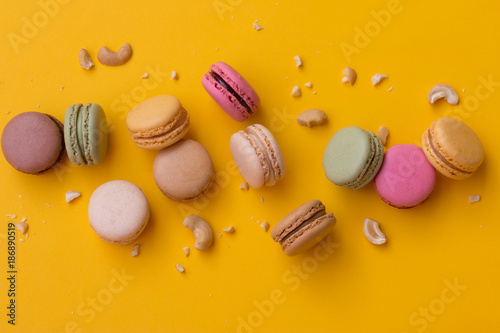 Poster Macarons Delicious macarons with pieces of nuts on yellow background.